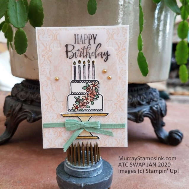 Stampin' Up! cake image colored in muted shades with a vellum stamped sentiment