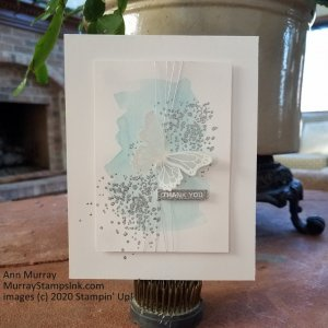 White embossed vellum butterfly on water color and silver embossed background